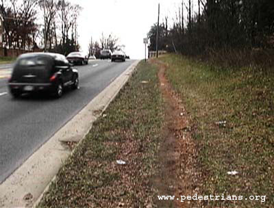 Photo - dirt path worn by pedestrian traffic along a busy road with no sidewalks.