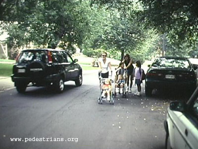 Mothers with strollers in street with traffic.