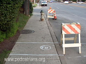 Old and planned WSSC hydrants block sidewalk.
